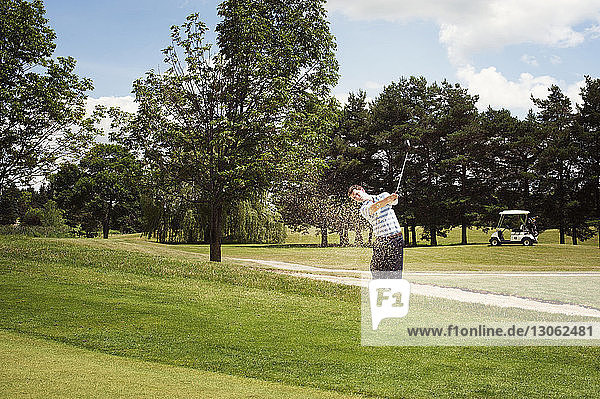 Young man swinging golf club at field