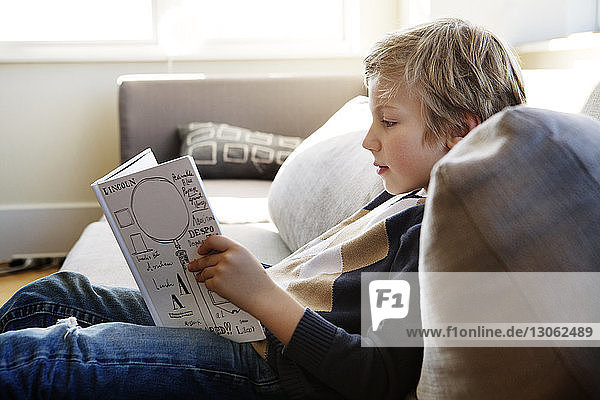 Boy studying while sitting on sofa at home