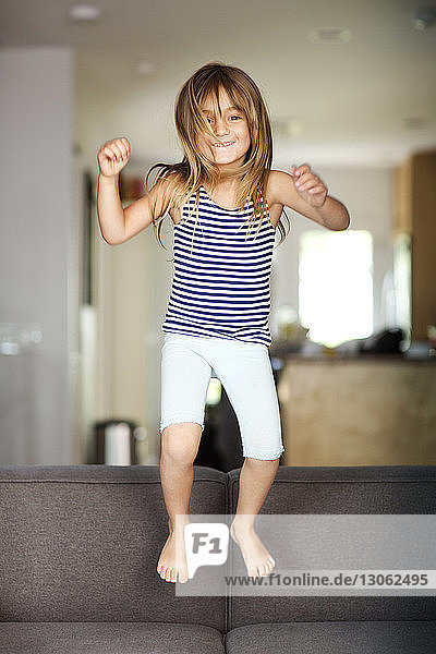 Portrait of cheerful girl jumping on sofa
