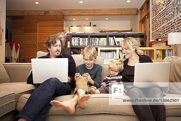 Geschwister benutzen Mobiltelefone  während sie mit den Eltern zu Hause auf dem Sofa sitzen