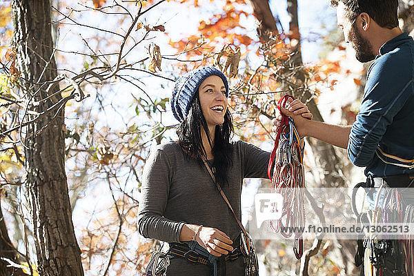 Freund gibt seiner Freundin Kletterausrüstung  während er an Bäumen steht