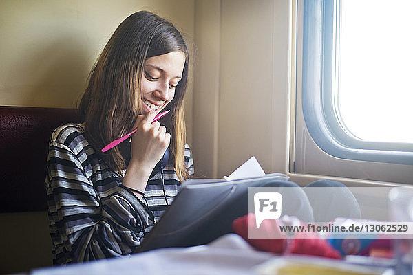 Lächelnde Frau betrachtet Buch während der Zugfahrt