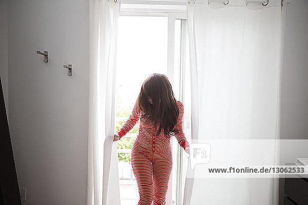 Frau hält Vorhang  während sie zu Hause am Fenster steht