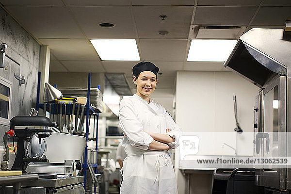 Portrait of happy chef with arms crossed standing in commercial kitchen
