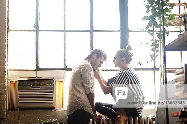 Seitenansicht einer Frau  die zu Hause mit den Haaren eines Mannes spielt