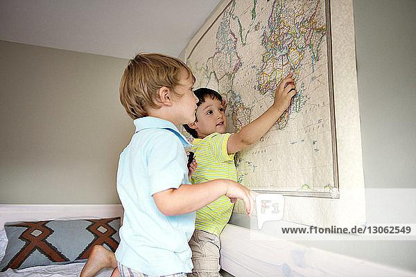 Siblings looking at map on wall