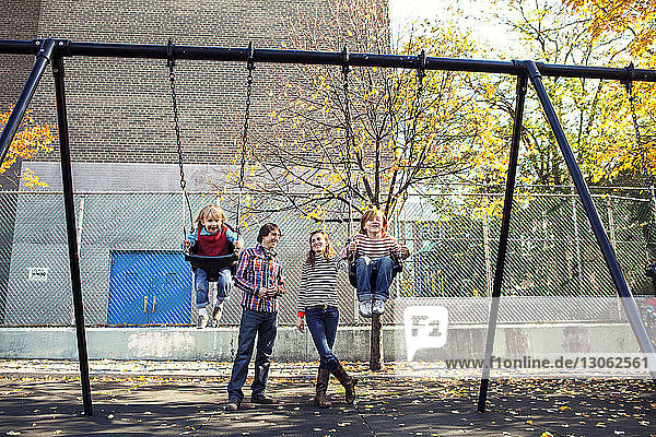 Parents standing while children swing at park