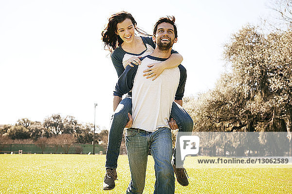 Mann nimmt Frau im Park huckepack