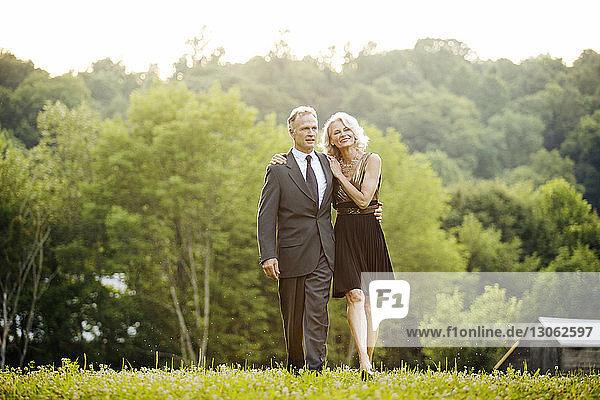 Happy senior couple walking on field against trees