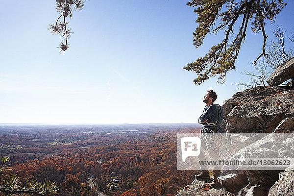 Nachdenklicher Mann mit verschränkten Armen auf Felsen stehend gegen den Himmel