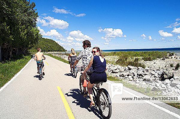 Freunde fahren Fahrrad auf der Straße gegen den Himmel an einem sonnigen Tag