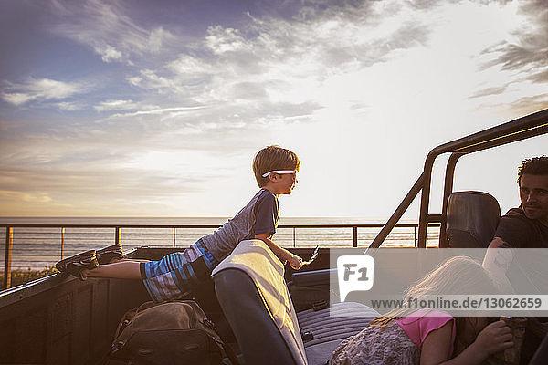Familie im Pickup am Meer bei Sonnenuntergang
