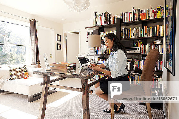 Side view of businesswoman working on table at home