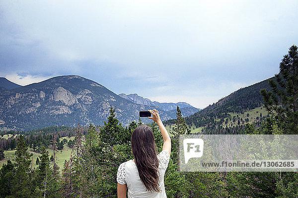 Rückansicht einer Frau  die Berge mit einem Smartphone fotografiert