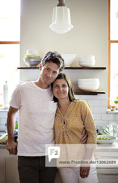 Portrait of happy couple standing in kitchen