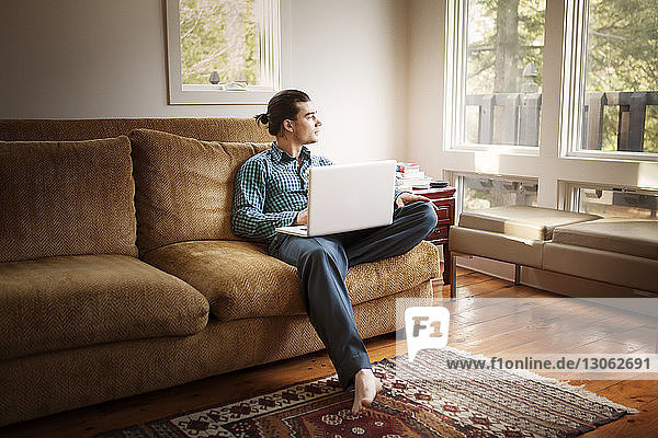 Man looking away while using laptop computer at home