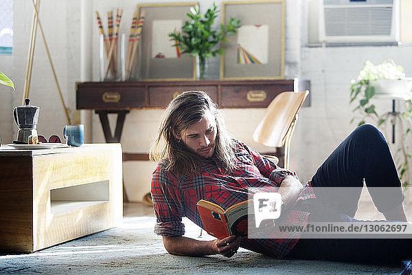 Mann liest Buch  während er zu Hause auf dem Boden liegt