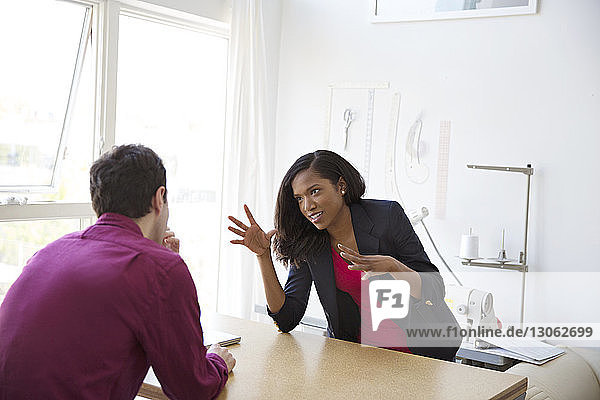 Business colleagues having discussion at desk in office