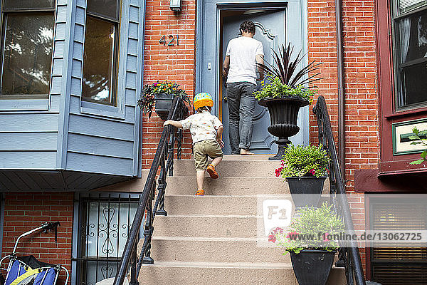 Low angle view of father and son on steps outside house
