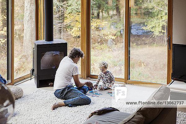 Hochwinkelansicht von Vater und Sohn beim Puzzlespielen zu Hause