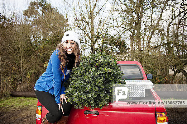 Portrait of woman with Christmas tree sitting on pick-up truck at backyard