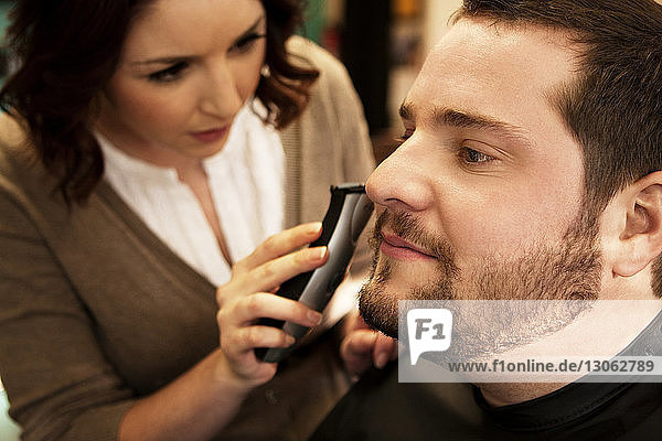 Close-up of female barber trimming beard of male customer in salon