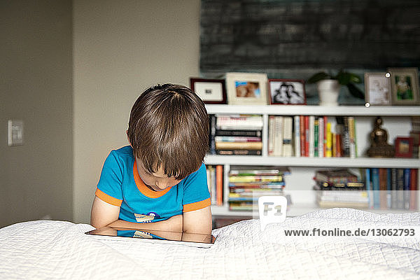 Boy using tablet computer while lying on bed at home
