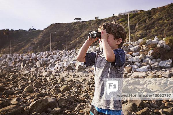 Junge schaut bei Sonnenuntergang durch ein Fernglas auf den Strand