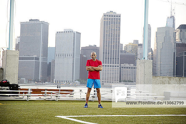 Portrait of confident senior man standing on soccer field in city