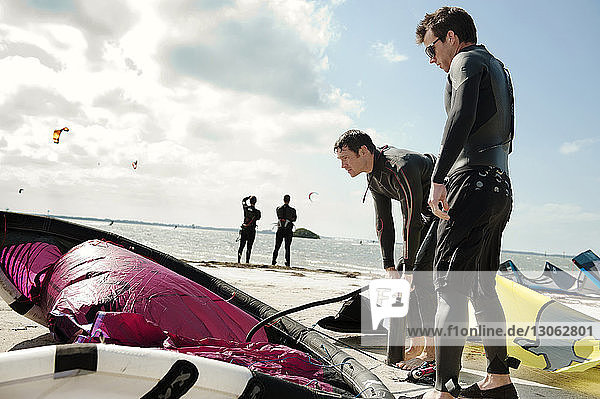 Mann füllt am Strand am Fallschirm Luft gegen den Himmel Mann füllt am Strand am Fallschirm Luft gegen den Himmel