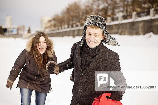 Glücklicher Mann hält im Park die Hand seiner Freundin