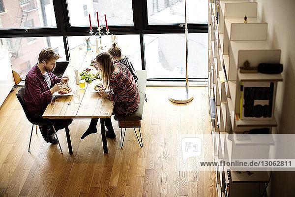 Hochwinkelaufnahme einer Familie beim Mittagessen am Tisch