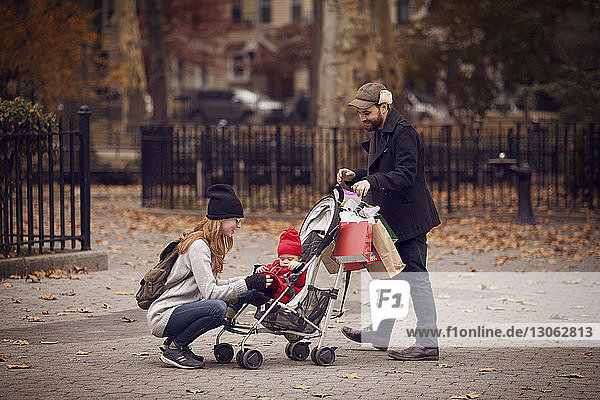 Man looking at woman keeping baby girl in baby stroller at park