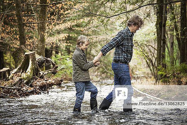 Seitenansicht des Vaters  der die Hand des Sohnes während der Flussüberquerung hält
