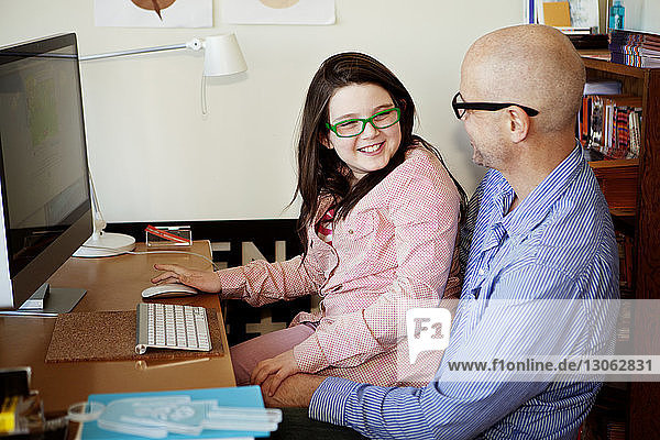 Father and daughter looking at each other while using desktop computer at home