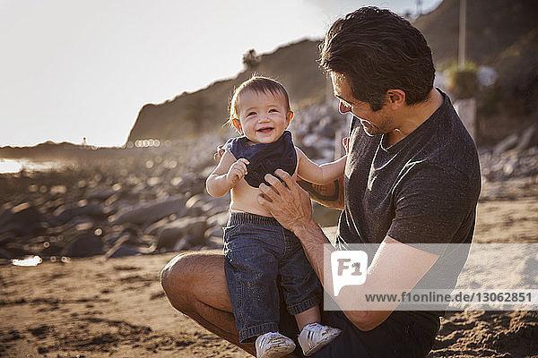 Vater mit fröhlichem Jungen am Strand