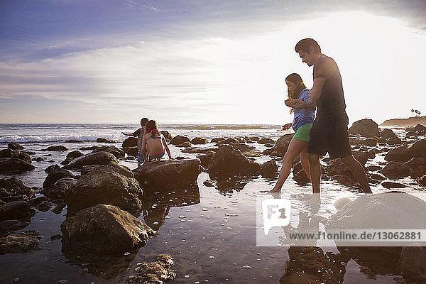 Familie geht bei Sonnenuntergang am Strand spazieren