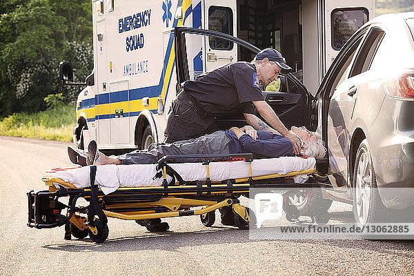 Rettungshelfer legt Patient im Auto auf Krankenhausbahre