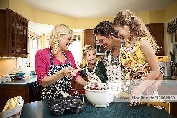 Glückliche Familie bereitet Cupcake in der heimischen Küche zu