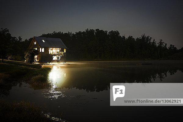 Ferienhaus im See gegen klaren Himmel bei Nacht