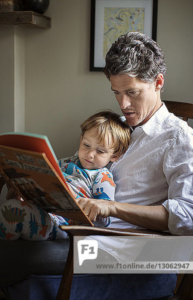Father reading picture book for son while sitting on chair at home