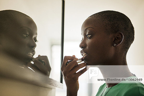 Side view of woman applying lipstick while standing by mirror at home