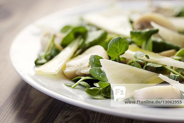 Nahaufnahme eines mit Käse garnierten Salats im Teller