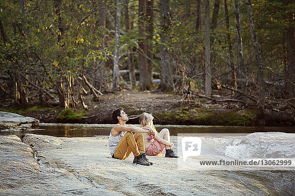 Couple looking up while sitting on rock by river at forest