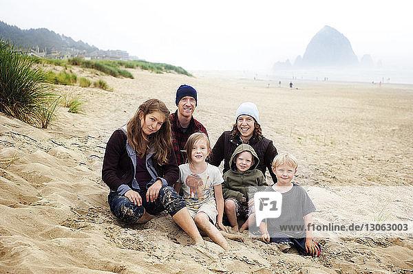 Porträt einer Familie  die auf Sand am Strand sitzt