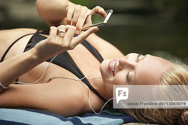 Woman using mobile phone while lying at riverbank