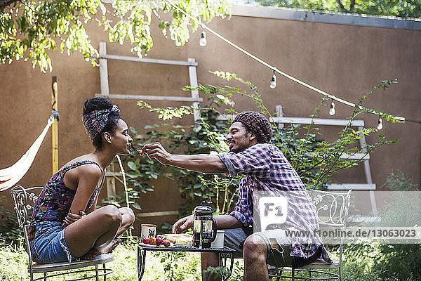Mann füttert Frau  während er auf einem Stuhl im Rasen sitzt