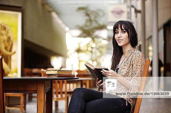 Porträt einer Frau  die ein Buch hält  während sie auf einem Stuhl im Strassencafé sitzt