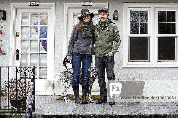 Porträt eines Ehepaares mit Hund auf der Veranda stehend