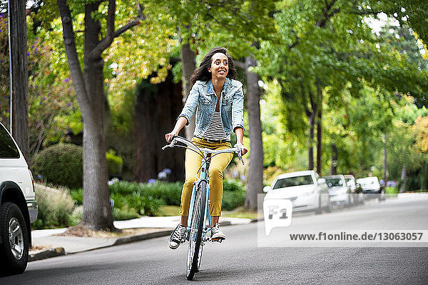 Woman looking away while riding bicycle on street